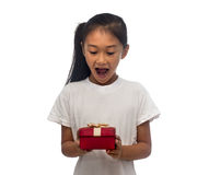 Lycklig asiatisk barnflicka med den röda gåvaasken royaltyfri foto