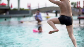 Lycklig asiatisk barnspring och banhoppning in till pölen Fps för ultrarapid 120