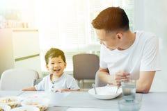 Lycklig asiatisk familj av fadern och sonen som spelar och skrattar, medan ha matställen royaltyfri fotografi