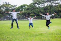 lycklig asiatisk familj, f?r?ldrar och deras barn som tillsammans in hoppar f?r att parkera o arkivbild