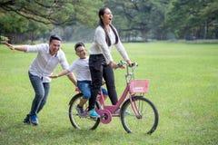 lycklig asiatisk familj, f?r?ldrar och deras barn som rider cykeln i f?r att parkera tillsammans fadern skjuter modern och sonen  royaltyfria bilder