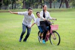 lycklig asiatisk familj, f?r?ldrar och deras barn som rider cykeln i f?r att parkera tillsammans fadern skjuter modern och sonen  arkivfoton
