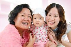 Lycklig asiatisk familj hemma Arkivfoto