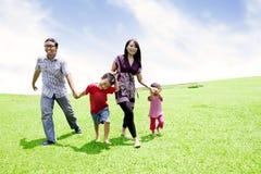 Lycklig asiatisk familj i äng Arkivbilder