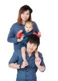 Lycklig asiatisk familj med ridtur på axlarnaställing royaltyfri fotografi