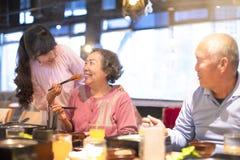 Lycklig asiatisk familj som har matställen royaltyfria foton