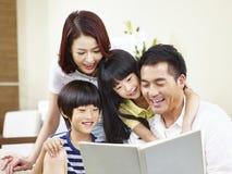 Lycklig asiatisk familj som hemma läser en bok arkivbild