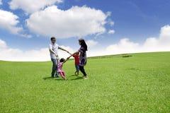 Lycklig asiatisk familj som spelar på fältet Fotografering för Bildbyråer