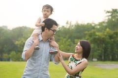 Lycklig asiatisk familj som tillsammans tycker om familjtid i parkera Royaltyfri Fotografi