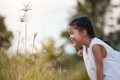 Lycklig asiatisk flicka för barn som två har roligt och spelar med naturen Arkivfoto
