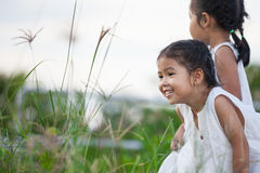 Lycklig asiatisk flicka för barn som två har roligt och spelar med naturen Fotografering för Bildbyråer