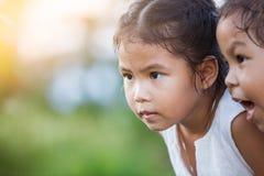 Lycklig asiatisk flicka för barn som två har roligt och spelar med naturen Arkivfoton