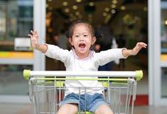 Lycklig asiatisk flicka f?r litet barn som sitter i sp?rvagnen under familjshopping i marknaden arkivfoton