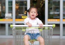 Lycklig asiatisk flicka f?r litet barn som sitter i sp?rvagnen under familjshopping i marknaden arkivbild