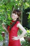 Lycklig asiatisk flicka i röd klänning Arkivfoto