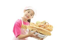 Lycklig asiatisk flicka med bröd royaltyfri foto