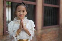 Lycklig asiatisk flicka med den thailändska traditionella klänningen Royaltyfri Bild