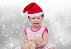 Lycklig asiatisk flicka med julhatten Arkivfoto