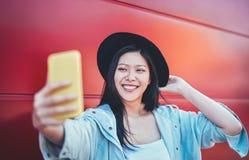 Lycklig asiatisk flicka som gör en video berättelse med den utomhus- mobila smarta telefonen - kinesisk kvinnarengöringsdukinflue fotografering för bildbyråer