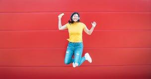 Lycklig asiatisk flicka som hoppar medan utomhus- lyssnande musik - galen kinesisk kvinna som har gyckel som dansar en sång mot r arkivfoton