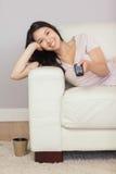 Lycklig asiatisk flicka som ligger på den hållande ögonen på tv:n för soffa Arkivfoto