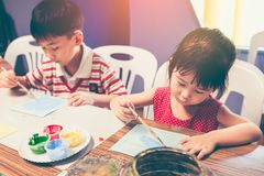 Lycklig asiatisk flicka som målar röd färg på konstverk med målarpenseln royaltyfri foto