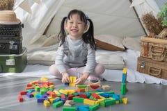 Lycklig asiatisk flicka som spelar med färgrika kvarter royaltyfri foto