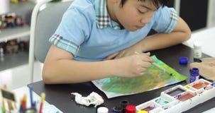 Lycklig asiatisk gullig färg för barnmålningvatten på papper med leendeframsidan, arkivfilmer
