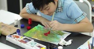 Lycklig asiatisk gullig färg för barnmålningvatten på papper med leendeframsidan, stock video