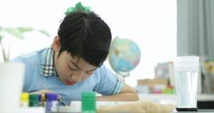 Lycklig asiatisk gullig färg för barnmålningvatten på papper med leendeframsidan, lager videofilmer