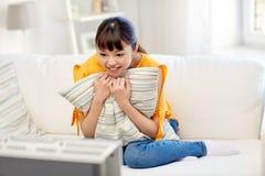 Lycklig asiatisk hållande ögonen på tv för ung kvinna hemma Royaltyfri Bild