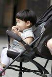 Lycklig asiatisk kines behandla som ett barn flickan äter mellanmålet på hennes behandla som ett barn sittvagnar royaltyfri fotografi