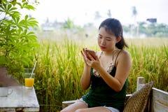 Lycklig asiatisk kinesisk kvinna på hennes 20-tal eller 30-tal som ler ha den roliga användande internet på mobiltelefonen som dr Royaltyfri Fotografi