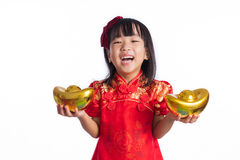 Lycklig asiatisk kinesisk liten bärande cheongsam och hållande guld in Royaltyfri Fotografi