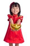 Lycklig asiatisk kinesisk liten bärande cheongsam och hållande guld in Royaltyfri Foto