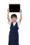 Lycklig asiatisk kinesisk liten chalkboar grundskola för barn mellan 5 och 11 årflicka som rymmer Royaltyfria Foton