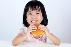 Lycklig asiatisk kinesisk liten flicka som äter hamburgaren fotografering för bildbyråer