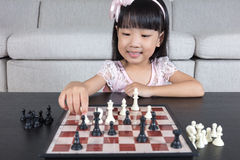 Lycklig asiatisk kinesisk liten flicka som hemma spelar schackschack Royaltyfri Foto