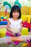 Lycklig asiatisk kinesisk liten flicka som inomhus spelar kinetisk sand arkivbilder