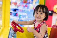 Lycklig asiatisk kinesisk liten flicka som kör Toy Bus Royaltyfria Foton
