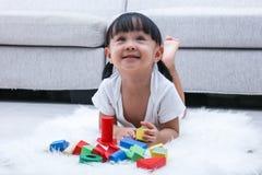 Lycklig asiatisk kinesisk liten flicka som spelar kvarter på golvet Arkivbild