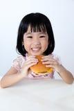 Lycklig asiatisk kinesisk liten flicka som äter hamburgaren Arkivfoton