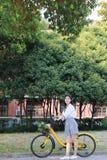 Lycklig asiatisk kinesisk nätt flicka som rider en dräkt för cykelkläderstudent i skola royaltyfria foton