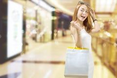 Lycklig asiatisk kvinna i den vita klänningen med shoppingpåsar på gallerian royaltyfria bilder