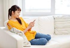 Lycklig asiatisk kvinna med den hemmastadda smartphonen Arkivfoton