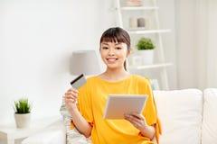 Lycklig asiatisk kvinna med den minnestavlaPC och kreditkorten Arkivfoto
