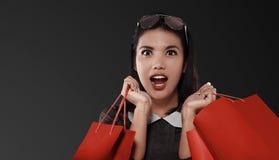 Lycklig asiatisk kvinna med den röda shoppingpåsen som firar Black Friday royaltyfri bild