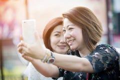 Lycklig asiatisk kvinna med vännen som tar en selfie arkivbild