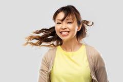 Lycklig asiatisk kvinna med vinkande h?r arkivfoton