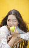 Lycklig asiatisk kvinna som eatting det gröna äpplet Arkivfoton
